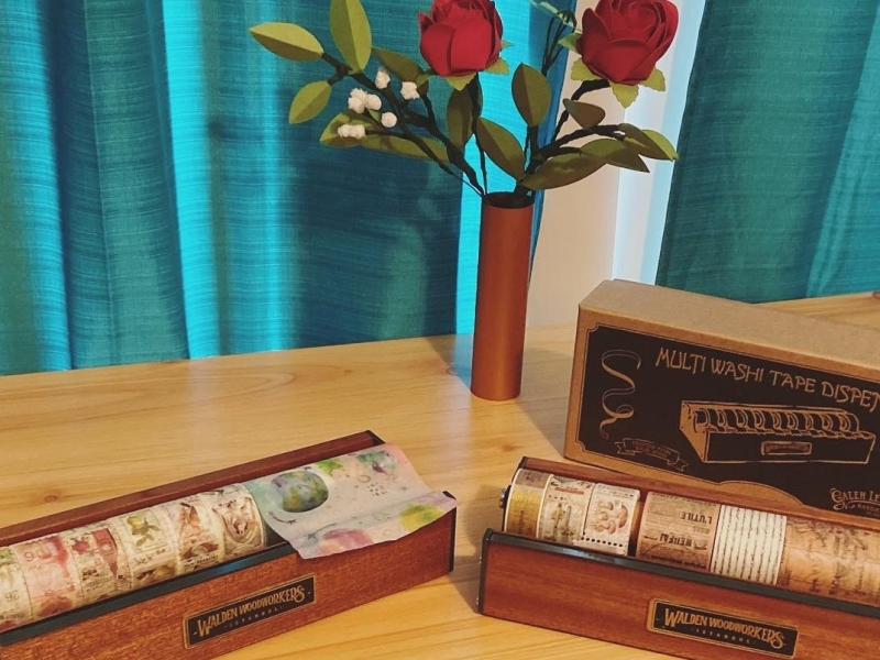 walden woodworkers wooden washi tape holders (mahogany) with a vase of red paper roses in the background