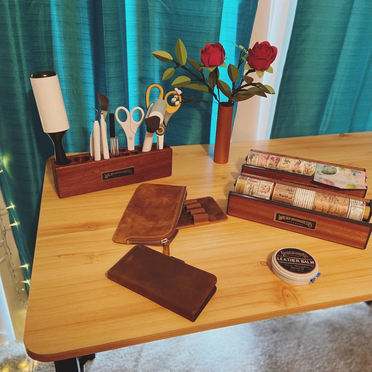 Wooden pen and tool holder, a vase of paper roses, two wooden washi tape dispensers, a leather slip-n-zip pen pouch, a brown leather detachable iPhone case, and a leather balm can be seen arranged on a table