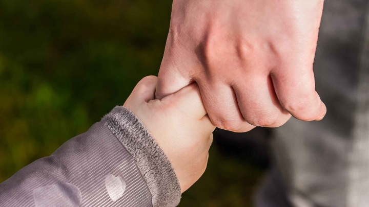 a baby hand holding an adult finger