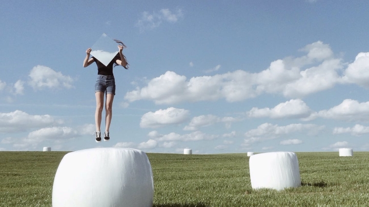 woman jumping with mirror on field